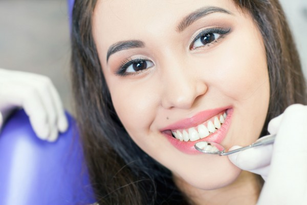 Implants - Young Women smiling with Dental mirror