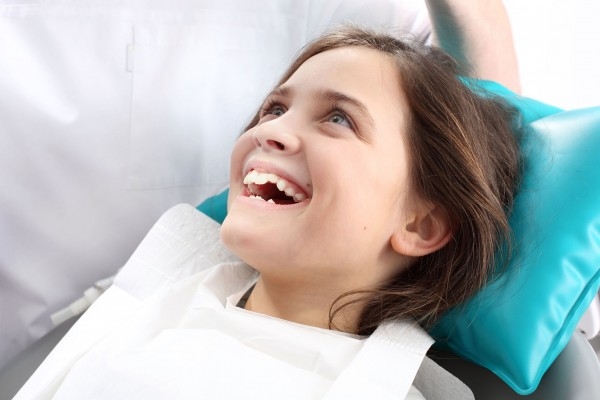 Sealant - girl in dental chair smiling
