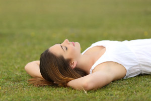 37323144 - relaxed woman lying on the grass sleeping in a tranquil scene with a green background